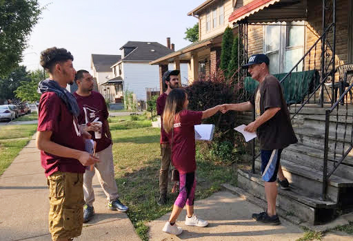 5 digital stewards apprentices shaking a neighborhood resident's hand at his front porch, while door knocking to tell people about the Equitable Internet Inititiave's gigabit internet connections