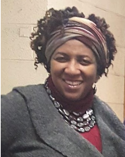 headshot of Monique smiling, wearing a jacket and a headscarf