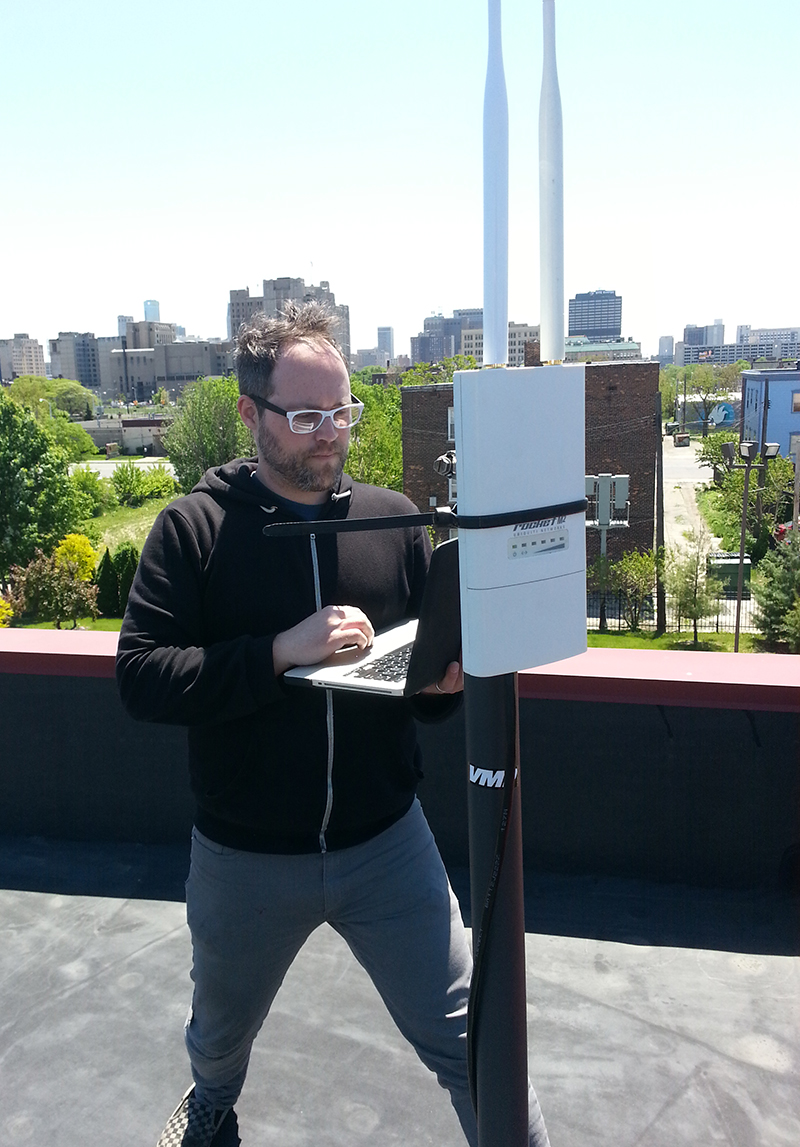 Anderson standing on a rooftop, holding a laptop next to a large wireless router mounted to the roof. City skyline in the background.